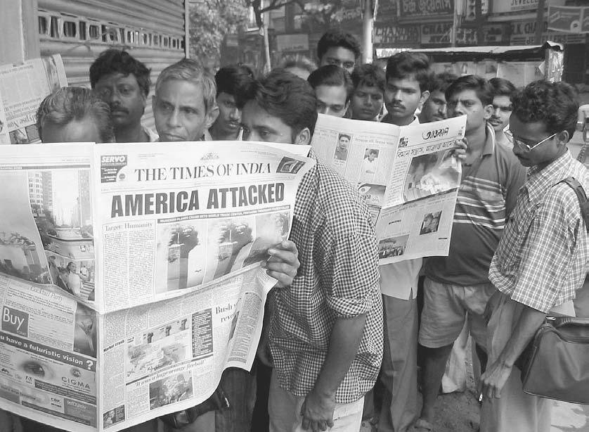NEWSPAPERS AND MAGAZINES 105 Indians waiting at a bus stop read details of the terrorist attacks in Washington, D.C.