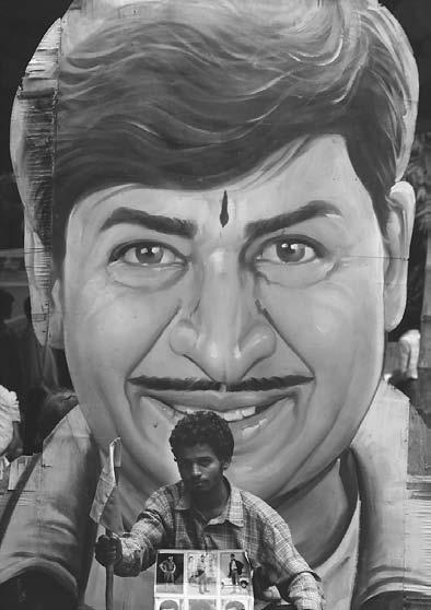 CINEMA 231 K. Nagaraj, an ardent fan of kidnapped superstar Rajkumar, stages a hunger strike in front of a huge cut-out of the actor in Bangalore, 9 August 2000.