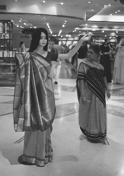 CONCLUSION 299 A woman stands next to a mannequin in a shopping center. Bangalore, 2001. (David H.
