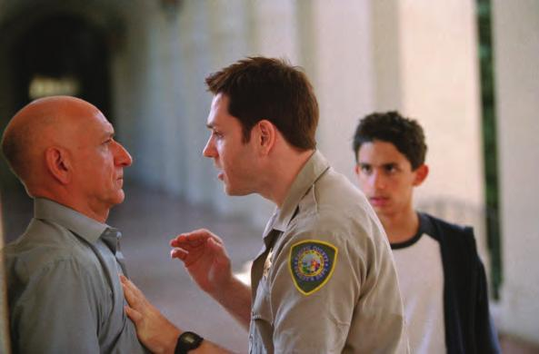 In the actual shot from the movie (2 5b), the power relationships are much clearer, as the bullying cop pushes an immigrant father literally against the wall, while his young son, slightly blurred