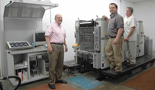 Rich Hopkins and his pressmen Chris DeLauder and Ron Doak standing on the Hamada B452 4-color offset press.